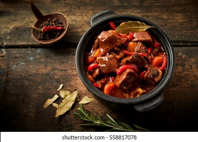 Overhead view of casserole full of hungarian goulash on ancient black background with decorative food arangement