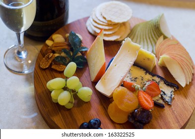Overhead view of a cheese and fruit platter with sparkling wine
