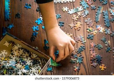 Overhead view - A child's had working on a puzzle, jigsaw, putting it together.