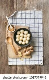 "Overhead view Chinese food sweet hot soup dessert ""Tangyuan""on rustic wooden table top."
