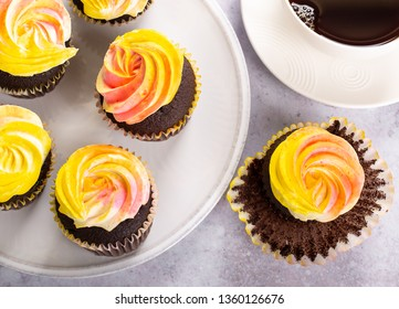 Overhead view of a chocolate cupcakes with colorful buttercream icing on a plate