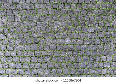 Overhead view of cobblestone street texture with grass. Stone pavement texture