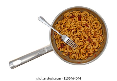 Overhead view of cold pasta with tomato chunks and seasonings with olive oil in a stainless steel skillet with a fork in the food isolated on a white background.