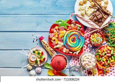Overhead view of colorful array of different childs sweets and treats in bowls on light blue wood background