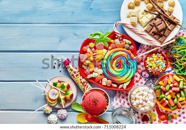 明るい青の木の背景にさまざまな子どものお菓子とお菓子のカラフルなアレイのビュー
