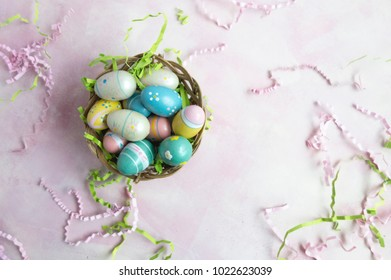 Overhead view of colorful Easter eggs in wicker basket on pink background with scattered pink and green Easter grass.