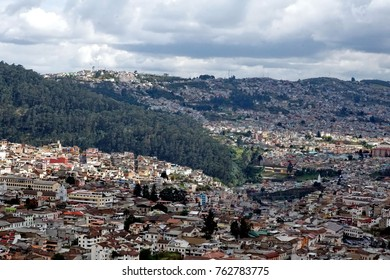 Overhead view of the colorful houses in the residential suburbs on the hills rising above Quito, Ecuador, seen from the top of the National Basilica