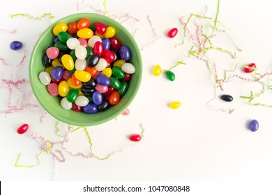 An overhead view of colorful jelly beans in a green bowl with scattered Easter grasson a white background.