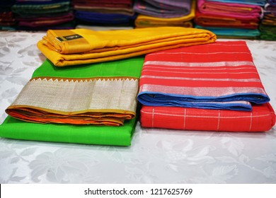 Overhead view of colorful Managalagiri cotton sarees on the display counter in a textile shop.