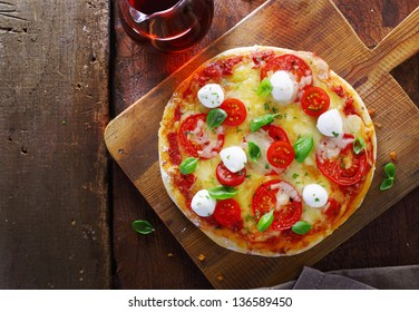 Overhead view of a colourful gourmet Italian pizza with a variety of cheeses, tomato and fresh basil on a wooden chopping board on an old rustic wooden table with copyspace