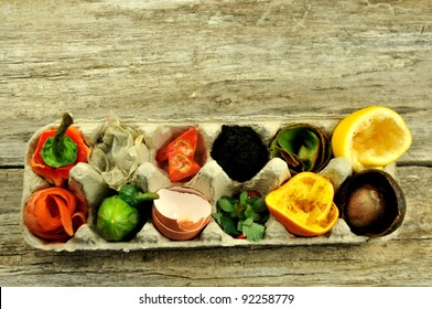 Overhead view of compost fruit and vegetables in egg carton, on rustic wooden background