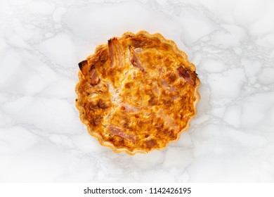 Overhead view of a cooked meat pie on a marble background