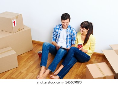 overhead view of couple moving in to new home and using wireless internet on tablet computer