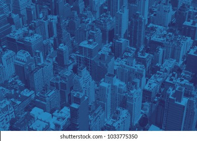 Overhead view of crowded buildings in downtown New York City with blue color cast effect