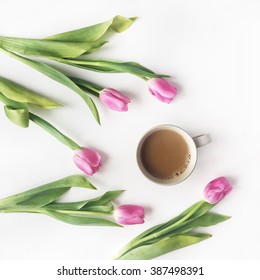 Overhead view of cup of coffee with milk and pink tulips isolated on white background. Flat lay, top view