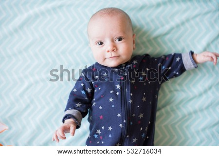 overhead view of cute baby boy laying on blanket looking up at camera