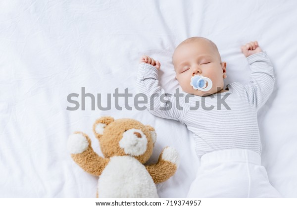 overhead view of cute baby with pacifier sleeping on bed with teddy bear