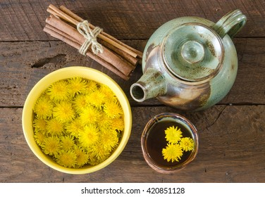 Overhead view of dandelion blossoms in a bowl and dandelion tea in a cup with a tea pot and bundled cinnamon