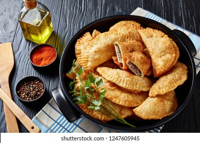 overhead view of deep fried turnovers or chebureki with a filling of ground beef meat and onion in a black ceramic pan on a wooden table, view from above, close-up
