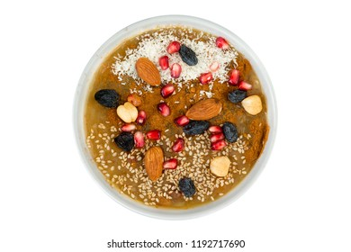 Overhead view of delicious asure bowl filled with nuts and fruit. White coconut powder sprinkled on top.