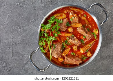 overhead view of delicious Beef and Okra Stew in a metal casserole on a concrete table, view from above, flat lay