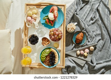 Overhead view of delicious breakfast in bed served on tray