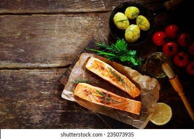 Overhead view of delicious grilled savory salmon cutlets with ingredients including a bouquet garni of fresh herbs, olive oil, tomatoes, baby potatoes and lemon on a rustic wood table with copyspace