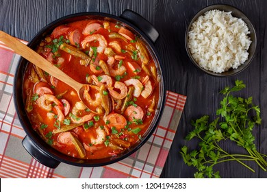 overhead view of delicious gumbo with prawns, okra, sausage in a dutch oven on a black table with bowl of white rice, horizontal view from above, close-up