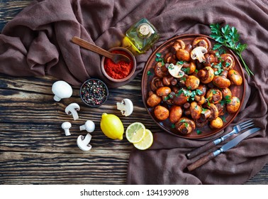 overhead view of delicious lightly fried champignons, Champinones Al Ajillo on an earthenware plate on an old rustic wooden table with brown cloth and ingredients, traditional spanish cuisine, flatlay