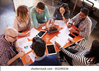 Overhead View Of Designers Having Meeting Around Table