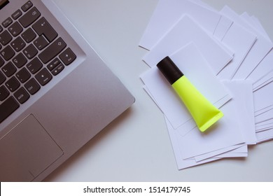 overhead view of a desk with a computer keyboard, a stack of paper notes and a yellow highlighter pen