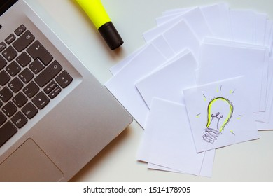 Overhead view of a desk with a laptoop, highlighter and a stack of notes and a sketch of a light bulb as in an Idea just came up
