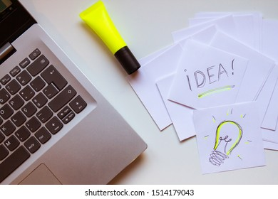 """Overhead view of a desk with a laptoop, highlighter and a stack of notes stating """"Idea"""" and the sketch of a light bulb as in an Idea just came up"""