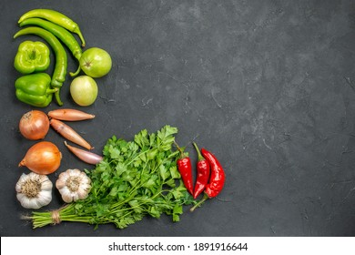 Overhead view of dinner background with a bunch of green and peppers onions and garlic on dark background