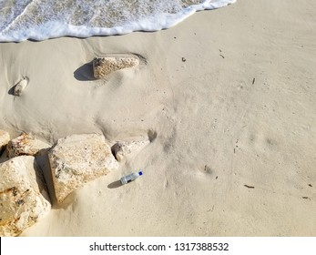 overhead view of discarded plastic water bottle on tropical beach