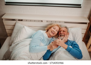 Overhead view of elderly couple lying in bed at bedroom. Senior couple enjoying spending time together.