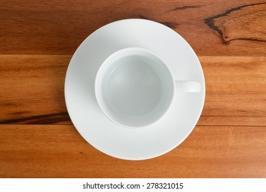 An overhead view of an empty espresso cup with a saucer.