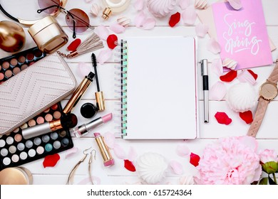 Overhead view of essential beauty items, Top view of cosmetics and female accessories. Notebook with empty white text space
