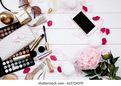 Overhead view of essential beauty items, Top view of cosmetics and female accessories, White wooden background with Flowers
