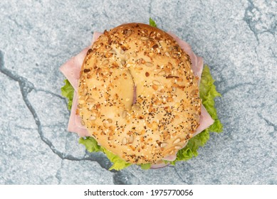 Overhead view of everything bagel bun envelops this non traditional ham sandwich loaded with lettuce, meat slices, and onion.