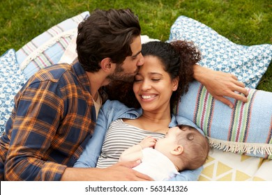 Overhead View Of Family With Baby Relaxing On Rug In Garden