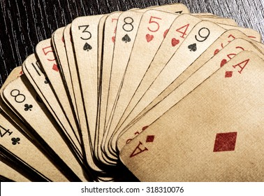 Overhead view of a fanned deck of old grungy discolored dirty vintage playing cards, conceptual of gambling and casinos