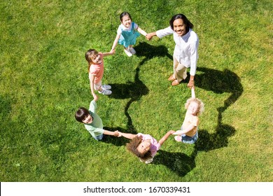 Overhead view female elementary teacher playing game of ring a roses with children on grass