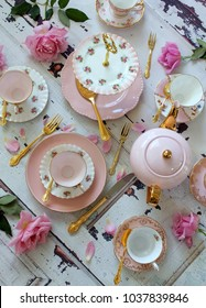 Overhead view flat lay vintage pink tea cups, cake stand, teapot, gold cutlery flatware, roses on distressed white wood table - high tea party