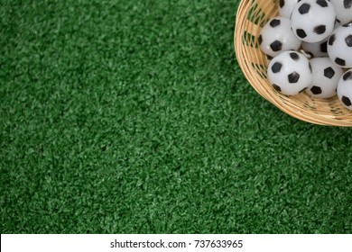 Overhead view of footballs in wicker basket on artificial grass