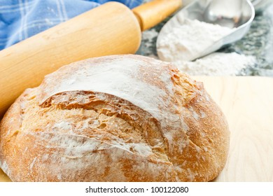 Overhead view of fresh baked artisan bread with enriched wheat flour and rolling pin in the background
