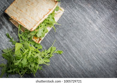 An overhead view of a fresh deli sandwich and salad on a granite countertop.