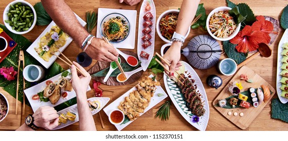 Overhead view of friends eating traditional Japanese food dishes served on the table. Set of sushi, rolls, spaghetti pasta, edamame, gyozas and tuna tataki.