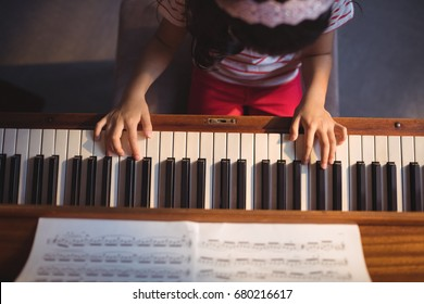 Overhead view of girl practicing piano in classroom at music school