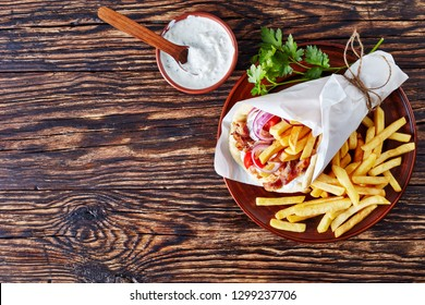 overhead view of greek souvlaki, pita ma gyros with chicken meat, vegetables, french fries on a earthenware plate and tzatziki sauce in a bowl on a rustic table, view from above, flatlay, copy space